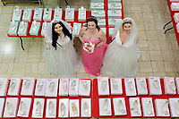 """COPY BY TOM BEDFORD<br /> Pictured L-R: Members of staff Lara Williams, Michelle Curry and Sara Morris who have been trying on some of the dresses at the John Pye Auctions warehouse in Pyle, south Wales, UK.<br /> Re: A bride cried tears of joy after her missing wedding dress was found among a pile of 20,000 gowns in a warehouse.<br /> Meg Stamp, 27, paid £1,300 for the beautiful ivory lace dress but it  was seized by liquidators after a bridal company went bust.<br /> It was boxed up along with 20,000 others and due to be sold for a knock-down price at auction.<br /> But determined Meg banged on the auctioneer door saying: """"I want my dress back"""".<br /> Staff at John Pye auctioneers in Port Talbot spent three hours sifting through boxes until they finally found Meg's dream dress."""