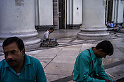 People take a break after lunch at the Grand post office in Kolkata, West Bengal, India,