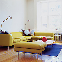 A chartreuse felted wool modular sofa by Terence Woodgate dominates a family room.  The flooring is a oak plank floor with a bevelled edge.