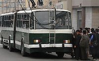 People queue to get on a packed trolley bus on the street of PyongYang, North Korea.
