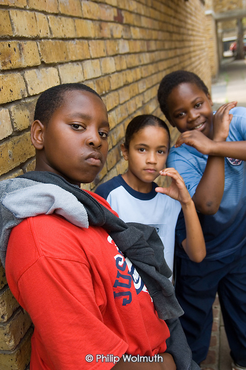 Young boys strike tough guy poses for the camera on Ashmole Estate, Oval, London.