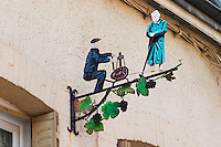 A wrought iron painted sign that illustrates the theme of champagne and wine production: A man in sitting at a bottling machine and a woman supervising the work, vine leafs and grapes, the village of Hautvillers in Vallee de la Marne, Champagne, Marne, Ardennes, France