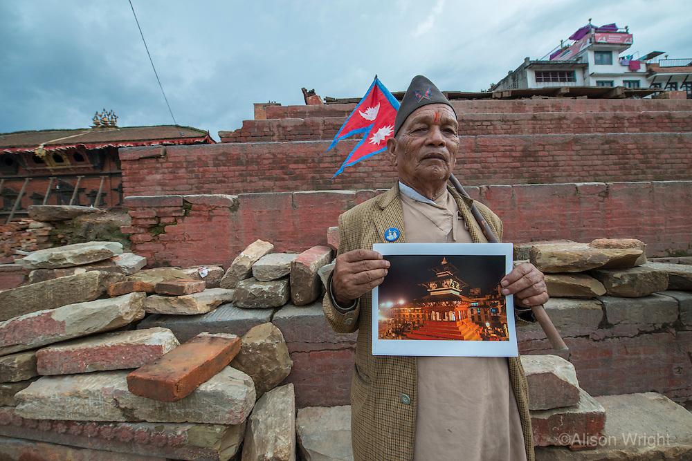 Nepal, Kathmandu, earthquake damage at Kathmandu Durbar Square. Man holding my photo of the where the same actual 16th century Hindu temple once stood. Man holding Nepali flag.