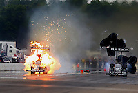 Aug 17, 2014; Brainerd, MN, USA; NHRA top fuel dragster driver Shawn Langdon (right) races alongside Terry McMillen who explodes an engine on fire during the Lucas Oil Nationals at Brainerd International Raceway. Mandatory Credit: Mark J. Rebilas-