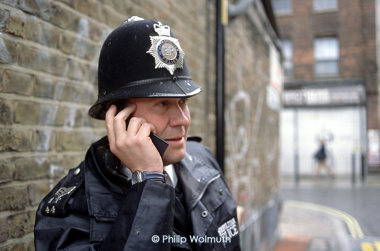 Sergeant Simpson, based  in the Brick Lane police office, uses a mobile phone while on patrol in Whitechapel, London.