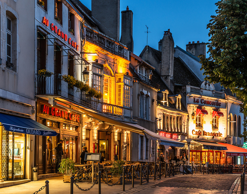 """A string of cafes light up the Place Carnot in the evening in spring, during the """"blue hour,"""" in Beaune, Burgundy, France."""