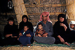 Marsh Arabs. Southern Iraq.  Marsh Arab man and two wives and children in reed constructed home. Haur al Mamar or Haur al-Hamar marsh collectively known now as Hammar marshes Iraq 1984