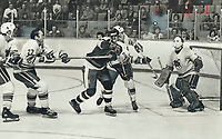 A big two-way effort: Frank Mahovlich (27) of Toronto s demonstrates he's also gifted in the art of hooking as he y restrains Quebec Nordiques' Rejean Houle from any forward advance on Toros' goalie Gilles Gratton. Other Toros in goalmouth action in last night's World Hockey Association game at the Gardens are Vaclav Nedomansky (left) and Rick Cunningham (3). Of more importance in Toros' 6-4 win was Mahovlich's offensive performance as he scored three goals, including clincher in third period. Crowd of 9,888 saw Toros' best game of season. <br /> <br /> 1976<br /> <br /> PHOTO :  Dick Darrell - Toronto Star Archives - AQP