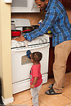17 month old toddler boy helping his father clean the stove