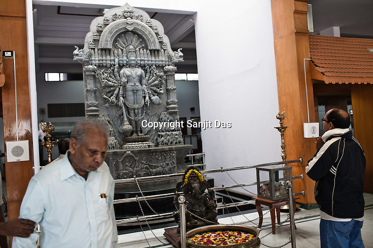 A man prays in front of the HIndu God's statue while an old man is escorted by a family member in the waiting lounge of the Narayana Hrudayalaya in Bangalore, Karnataka, India. Photo: Sanjit Das/Panos