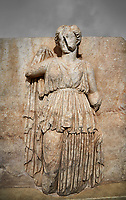 Roman Sebasteion relief sculpture of Ethnos with belted peplos, Aphrodisias Museum, Aphrodisias, Turkey.  Against a grey background.<br /> <br /> The matronly figure wears a belted classical dress (peplos) and held her long cloak up behind. The square hole above her shoulder with a corresponding hole in the back, was for lifting the finished relief into the ancient building by crane.