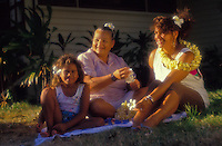 Local polynesian family relaxing out on the lawn in the sun and wearing leis