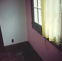 Corner of empty room with single yellow curtain<br />