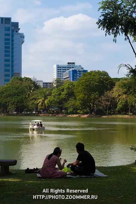 Tourists having a picnic near a lake in Lumpini park, Bangkok, Thailand