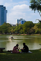 Tourists having a picnic near a lake in Lumpini park, Bangkok, Thailand