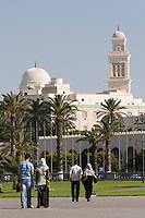 Tripoli, Libya, North Africa - Young Libyan Men's and Women's Clothing Styles as seen in Public Park near the Green Square, downtown Tripoli.  Al-Jaza'ir Mosque in the background.