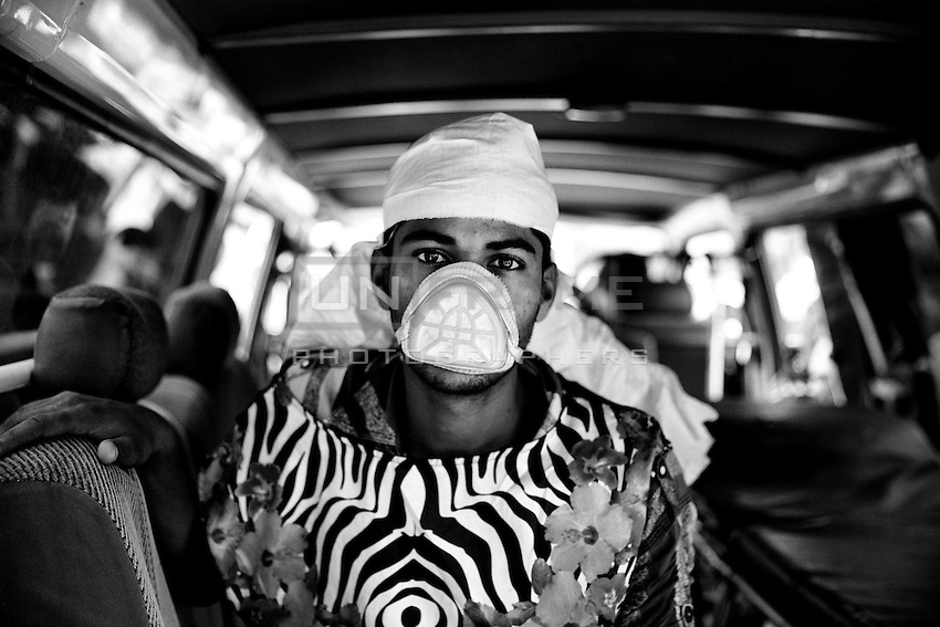 A rescue worker waits inside of the ambulance as part of its medical service during the rescue operation at the site of Savar tragedy.  Savar, near Dhaka, Bangladesh