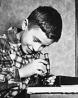 Young scientist and microscope.