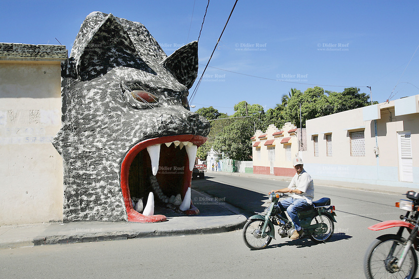 Dominican Republic. San Juan Province. San Juan de la Maguana. Two motorbikes on the concrete road pass by the derelict entrance of a disco place, the jackal. The animal has the mouth wide open and shows white teeth. © 2006 Didier Ruef