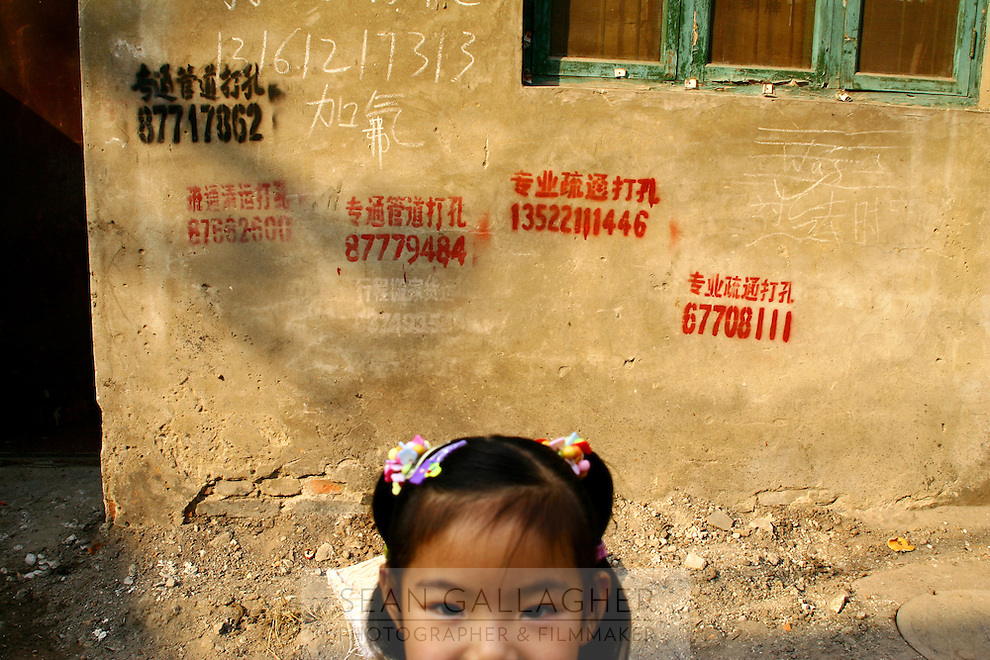CHINA. Beijing. A young girl in a 'hutong' (traditonal home) that is being destroyed to make way for new developments aimed at modernising the city for the 2008 Summer Olympics. Cellphone numbers daub walls, left by people looking for work and people offering work. 2005