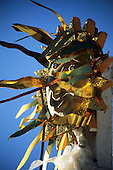 Salvador, Brazil. Crude sparkly gold carnival float mask glittering in the sun. Bahia State.