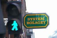 A neon sign for Systembolaget the Swedish monopoly for retail sales of alcohol behind a pedestrian crossing light with a green man indicating go walk Stockholm, Sweden, Sverige, Europe