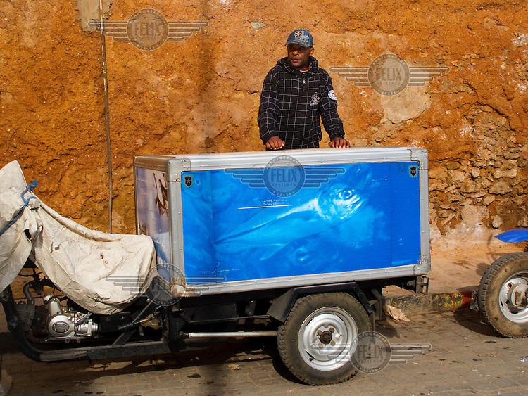 A man sells fish by the Medina wall from a refrigerated box carried on a converted motorbike.