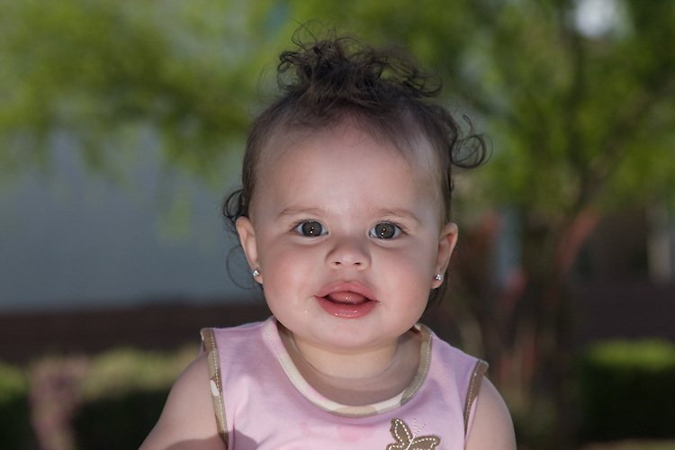 A baby focuses on the camera during a portrait shoot.