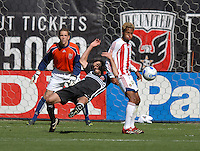 Chivas USA defender Lawson Vaughn (25) holds and fouls DC United midfielder Ben Olsen (14) in front of DC United goal keeper Troy Perkins (1). DC United defeated Chivas USA 2-1, at RFK Stadium in Washington DC, Sunday May 6, 2007.