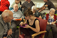 "Switzerland. Canton Ticino. Gordola. Casa Riposo (Retirement Home) Solarium. MOPS_DanceSyndrome is an independent Swiss artistic, cultural and social organisation operating in the field of contemporary dance and disability. It is composed only of Down dancers. Gaia Mereu (C) is enjoying a slice of chocolate cake after the ""Choreus Numinis""  show. She seats on a chair and talks to an elderly old man. Down syndrome (DS or DNS), also known as trisomy 21, is a genetic disorder caused by the presence of all or part of a third copy of chromosome 21 It is usually associated with physical growth delays, mild to moderate intellectual disability, and characteristic facial features. A group of elderly people, all seated in wheelchairs, look at the woman dancing. A retirement home – sometimes called an old people's home or old age home - is a multi-residence housing facility intended for the elderly. Gordola is a municipality in the district of Locarno. 29.11.2019 © 2019 Didier Ruef"