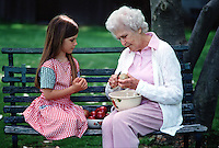 Grandmother and granddaughter peeling apples outdoors.