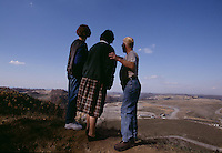 """Larry Gibson (right) leads women to a knoll in the family cemetery on Kayford Mountain near Cabin Creek to overlook sprawling Catenary Coal Company's Samples Mine owned by Arch Coal Company. <br /> <br /> Larry Gibson's family has lived on or near Kayford Mountain since the late 1700's. More than 300 relatives are buried in the cemetery on Kayford Mountain. Larry and his family used to live on the lowest lying part of the mountain, and looked """"up"""" to the mountain peaks that surrounded them. Since 1986, the slow motion destruction of Kayford Mountain has been continuous -- 24 hours a day, seven days a week. Eighteen years after the """"mountain top removal"""" project began, Larry Gibson now occupies the highest point of land around; he is enveloped by a 12,000 acre pancake in what was previously a mountain range.<br /> <br />  The coal company wanted to buy the property to expand their operation, but he formed a nonprofit foundation of the Stanley family heirs when their 500 acres shrunk to 50 acres (the coal company had acquired the rest.)  The heirs have a few small houses and a park they invite family and friends to gather on holidays for cookouts and song fests.  During every gathering, people always make their way to the old family cemetery where mining can be viewed (one of the few places on private land to see an operation from the ground). Fly rock from mining blasts has landed in the cemetery.  Gibson has been intimidated, harassed and threatened by mining company employees for holding out.  He remains outspoken against mountaintop removal."""