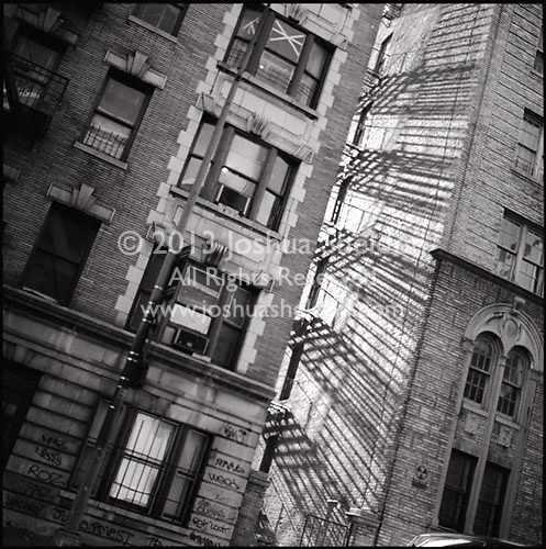 Shadows of fire escape on apartment building<br />