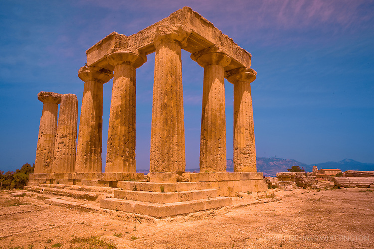 The surviving Doric columns of the Temple of Apollo stand tall amongst the Greek ruins in Ancient Corinth.
