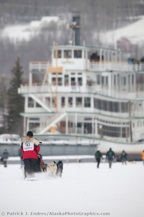 Dog Musher Mitch Seavey mushes past the Historic Riverboat Discovery along the Chena River, for the 1000 mile 2003 Iditarod sled dog race from Fairbanks to Nome, Alaska . Lack of snow along the normal trail route further south forced the relocation of the restart on the Chena River in Fairbanks.