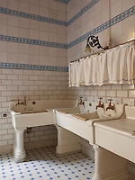 Sturdy enamel sinks line a corner of the kitchen with walls clad in white tiles and rows of blue tiles with a flower motif