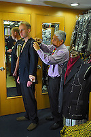 Sam measures a tourist for a suit jacket in Sam's Tailors shop at Nathan road, Hong Kong. Sam is the founder of Sam's Tailors, one of the best known in Hong Kong. He has dressed presidents, royalty, and even the pope. .04 May 2006