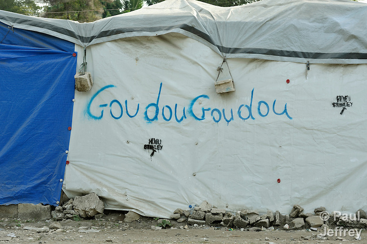"""""""GoudouGoudou,"""" the Kreyol word that Haitians have come to call the earthquake that ravaged parts of their country in in January 2010, is scrawled on the wall of a tent in a camp in Grand-Goave, Haiti, where families left homeless by the quake continue to live. The word was derived from the sound that many recall the quake producing as their houses moved and collapsed. The ACT Alliance has supported families in this camp with a variety of services, and has rebuilt a school beside the tent city."""