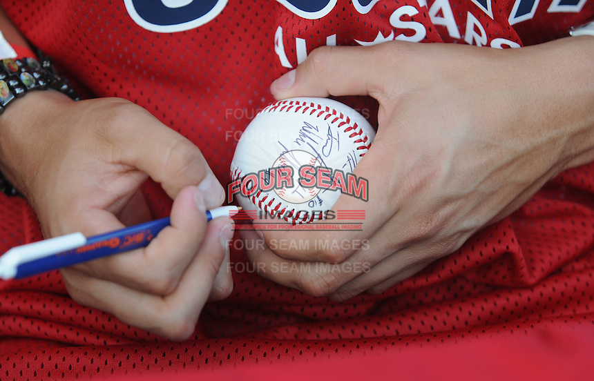 Wilmer Flores of the Savannah Sand Gnats signs a ball at the 2010 South Atlantic League All-Star Game welcome party and festivities Monday night June 21, 2010, at the Wyche Pavilion along the Reedy River in Greenville, S.C. Photo by: Tom Priddy/Four Seam Images