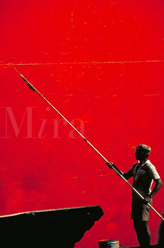 A worker with a long handled roller brush paints a ship's hull bright orange. occupations, trades,. Guayaquil, Ecuador.