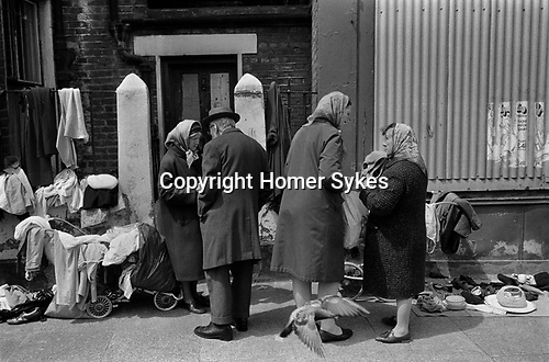 Whitechapel, London. 1972<br /> Unemployed woman sell old clothes and bric-a-brac from prams to supplement their meagre living. One wears her headscarf over her hat to keep out the cold.
