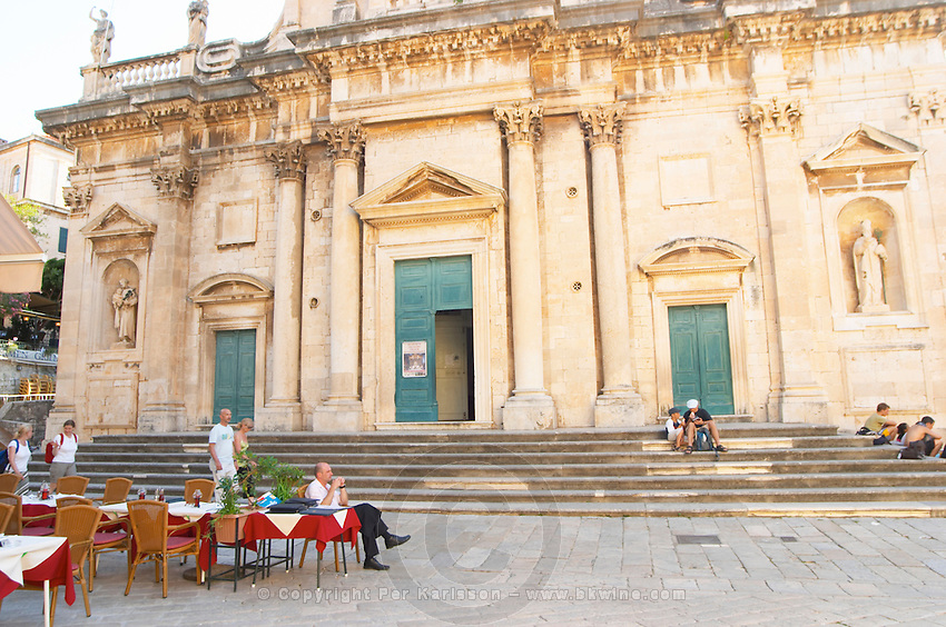 A cafe restaurant with outside seating terrace in front of the Cathedral of the Assumption of our Lady. A man sitting on a chair. Dubrovnik, old city. Dalmatian Coast, Croatia, Europe.