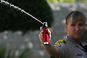 San Diego Sheriff Department Sgt. Amy Brown demonstrates shooting the pepper spray cannister she carries on her belt in 2009.  photo for the North County Times
