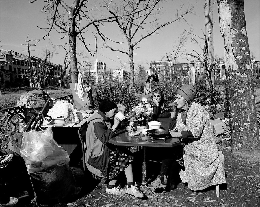 Grozny, Chechnya, March 1995..Civilians living in an underground bunker drink tea outside with plastic flowers on the table..