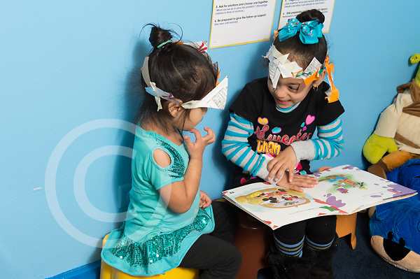 Education preschool 3-4 year olds two girls in play hats they made playing game with book