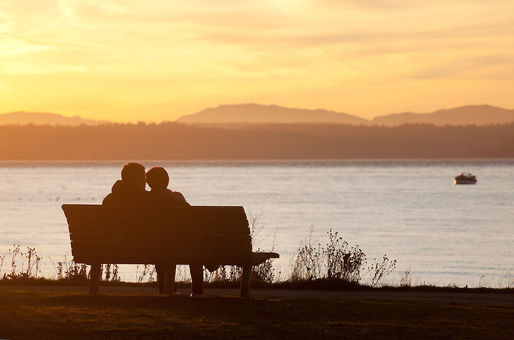 Seattle, Golden Gardens park, Puget Sound; Lovers on a bench, winter sunset, Olympic Mountains, Pacific Northwest. Washington State, U.S.A.,