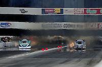 Feb. 12, 2012; Pomona, CA, USA; NHRA funny car driver Alexis DeJoria (right) races alongside John Force during the Winternationals at Auto Club Raceway at Pomona. Mandatory Credit: Mark J. Rebilas-