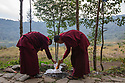 India - Sikkim - Buddhist monks light a fire next to Khecheopalri sacred lake.