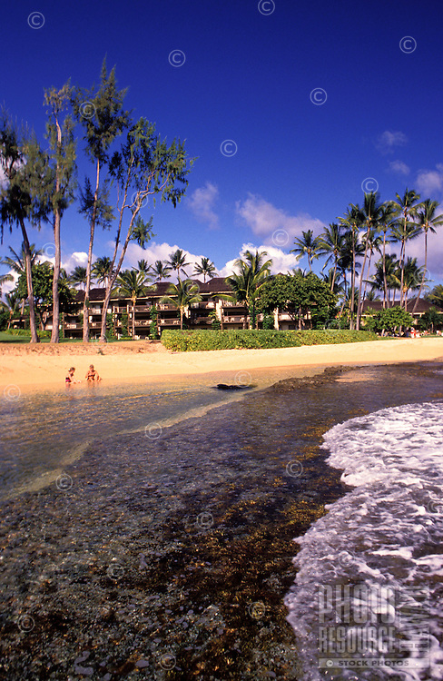Two people playing at the beach in front of Lae Nani resort, Wailua, Kauai