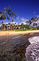 Two people playing at the beach in front of Lae Nani resort, Wailua, Kauai